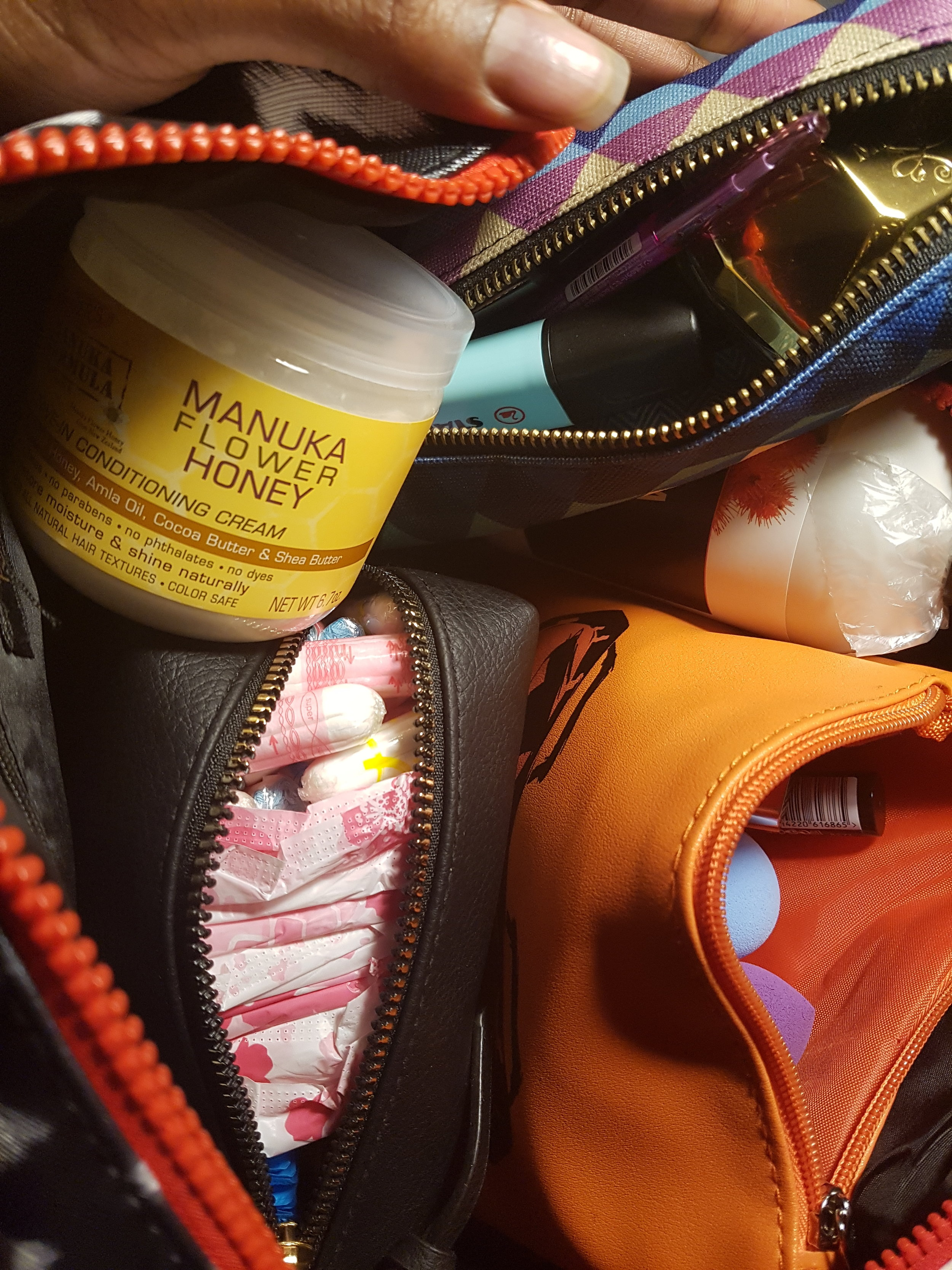 In one packing cube: natural hair shampoo and conditioner, feminine care and birth control, pencil case, make-up bag