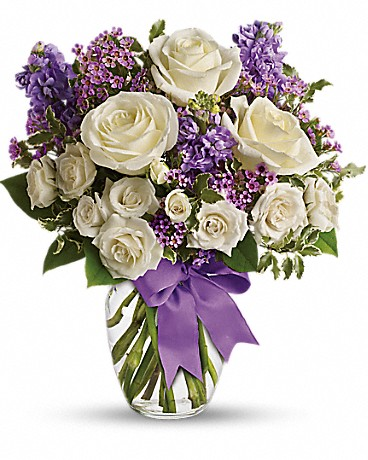 Enchanted Cottage    This magical bouquet will be at home in a cottage, a condo, a studio or an estate. Enchant someone today! White roses and spray roses, lavender stock and waxflower, all perfectly arranged in a clear glass vase that's wrapped with purple ribbon.    Buy Now>>