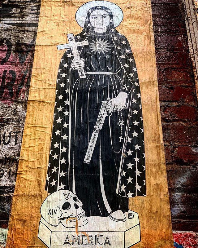 Forgive the angle, but this piece was up high!! So much to unpack with this one, certainly tag the artist if you know who made this.... that said, let's get into it — the subject is wearing a cloak covered in stars which also has a crossbones on the sleeve. She has a halo, and in her right hand a cross with a $, an outline of Jesus, and a bundle of 5 arrows which tends to signify strength. The Eye of Providence is on her chest, surrounded by sunbeams. In her left hand she holds a firearm which is inscribed with the Latin, 'Silentium Est Aureum' which means 'silence is golden.' The gun also has 13 hashmarks & is accompanied by a rosary which also has interlocked triangles hanging from it, perhaps hinting at the trinity. She stands on a pedestal titled AMERICA, which also includes a skull with the Roman numeral for 14 & a crossed set of old keys. While I love unpacking the elements in art, I usually stop short of making too many assumptions. That said, the interweaving of the stars on the cloak, the gun, and the various odes to Christianity seem to be a strong commentary on the American achilles heal — the way patriotism, violence, and religion come together to subjugate. Art FTW. #streetart #nycart #wheatpasteart #religiousart #americanart #nycstreetart #soho #sohonyc