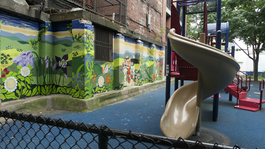 childrens play area littered with trash, alcohol bottles and needles