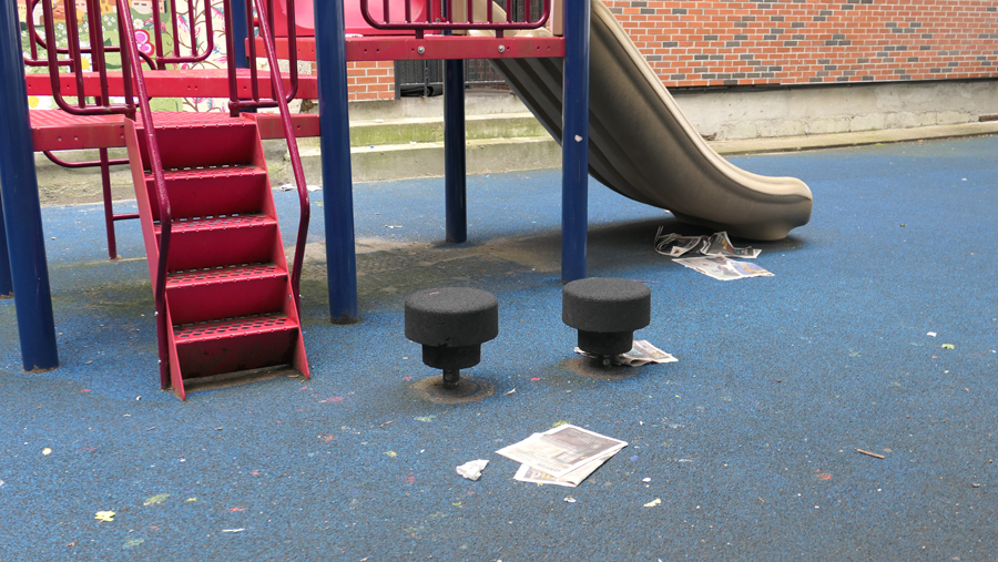 photo shows newspapers and trash by the childrens slide