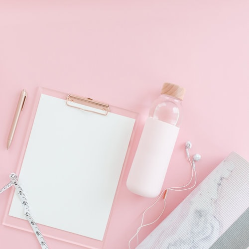 Pink background with white clipboard, white water bottle, and a marble rolled up yoga mat.