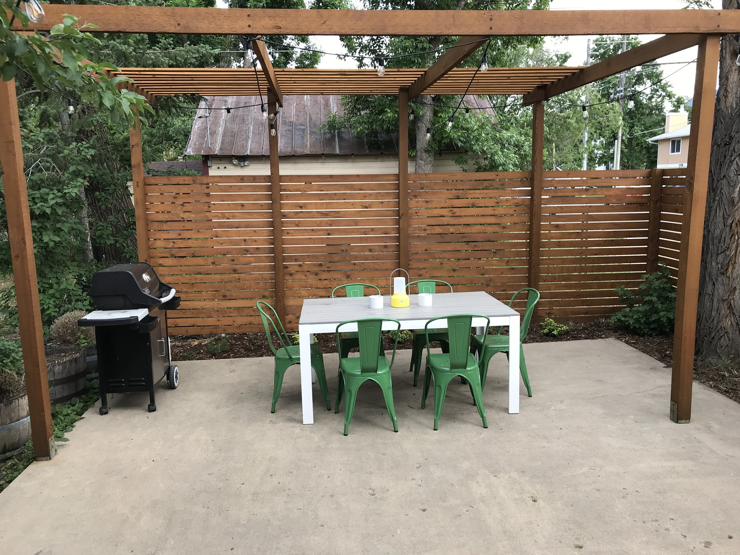 Large, private patio and yard with gas grill and outdoor dining area.