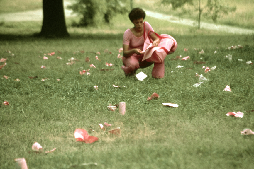 Maren Hassinger,  Pink Trash , 1982. Courtesy of the artist. [Image Description: A woman wearing pink kneels in a grassy field. She holds a pink duffel bag and is holding pink pieces of paper. Scattered around the grass are pieces of trash that are also painted pink.]