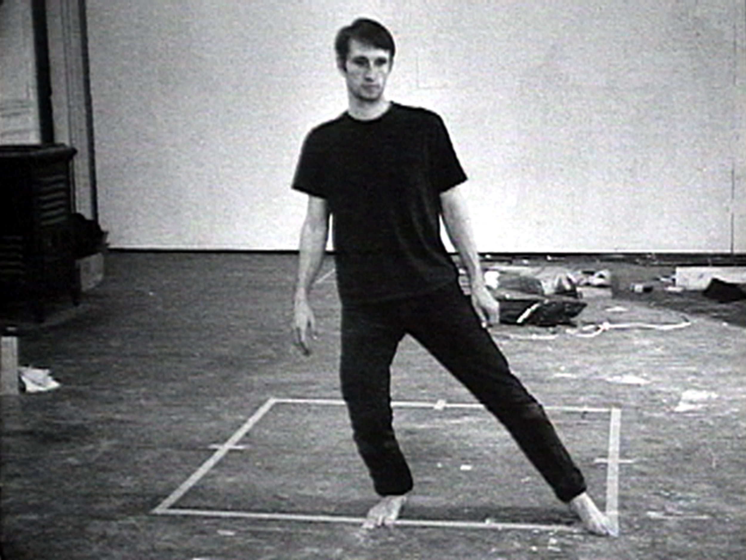 Bruce Nauman,  Dance or Exercise on the Perimeter of a Square (Square Dance) , 1967-68. Courtesy Electronic Arts Intermix (EAI), New York. [Image Description: A black and white image of a man standing in the center of a room, facing outwards, wearing a black t-shirt and black pants. On the floor is a taped outline of a square. The man stands on one edge of the square, and stretches one leg out to the corner, touching it with his toes.]