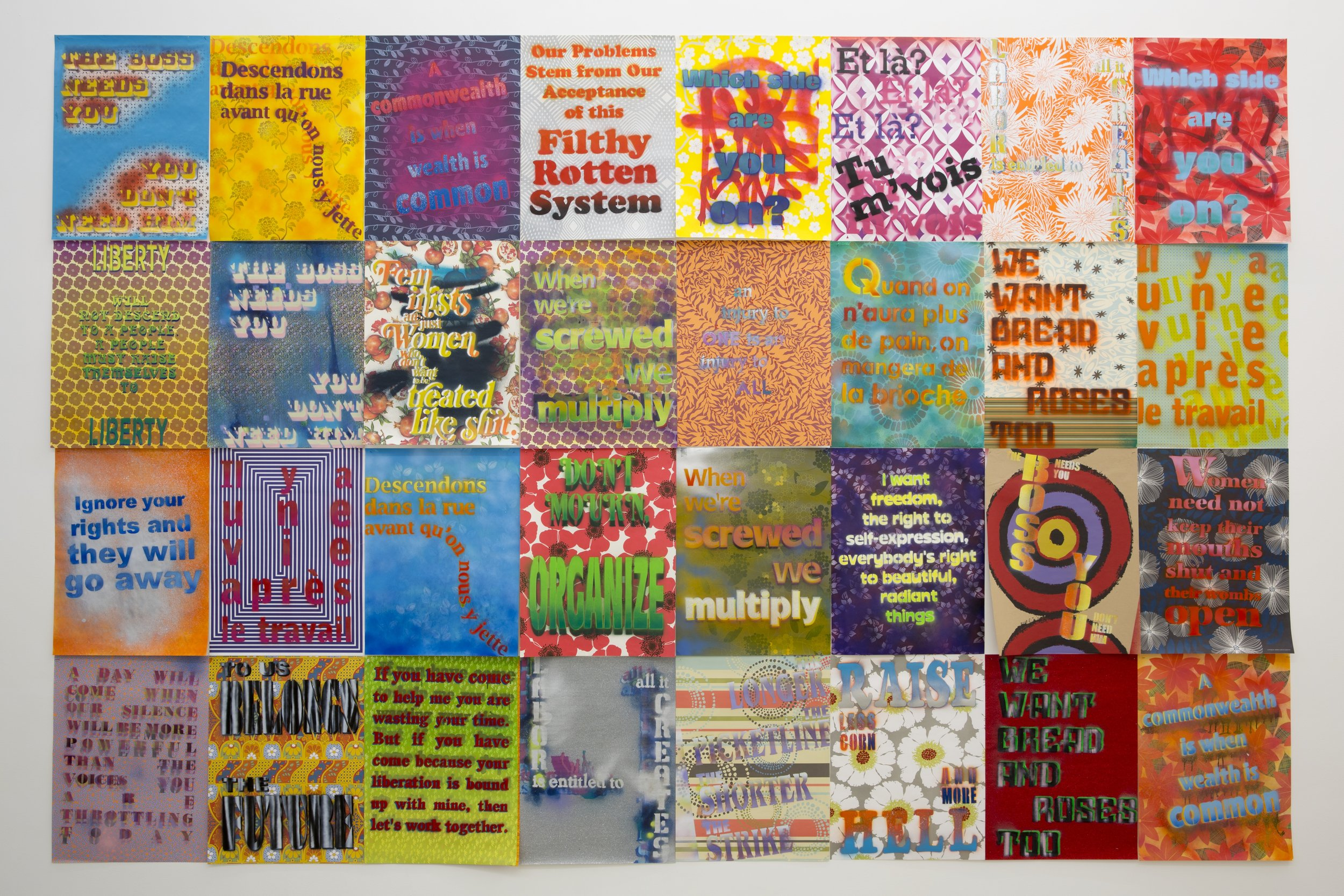 """Andrea Bowers,  Workers' Rights Posters , 2013. Image courtesy of the artist and Andrew Kreps Gallery, New York. [Image Description: A grid of 32 rectangular posters, 4 rows high and 8 columns across. The posters are rendered in a variety of bright colors and patterns, and feature repeating phrases that include """"When we're screwed we multiply,"""" """"Ignore your rights and they will go away,"""" """"Don't Mourn, Organize,"""" """"Acceptance of this filthy rotten system,"""" and """"Women need not keep their mouths shut and their wombs open.""""]"""