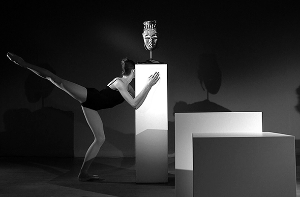 Brendan Fernandes,  As One I , 2015. Silver Gelatin Print. Commissioned by Seattle Art Museum. [Image Description: A black and white photograph features a female dancer and three white, rectangular pedestals. The dancer, wearing a black leotard and ballet shoes, balances against the tallest pedestal at the center of the image, which features a mounted, carved mask on top.]