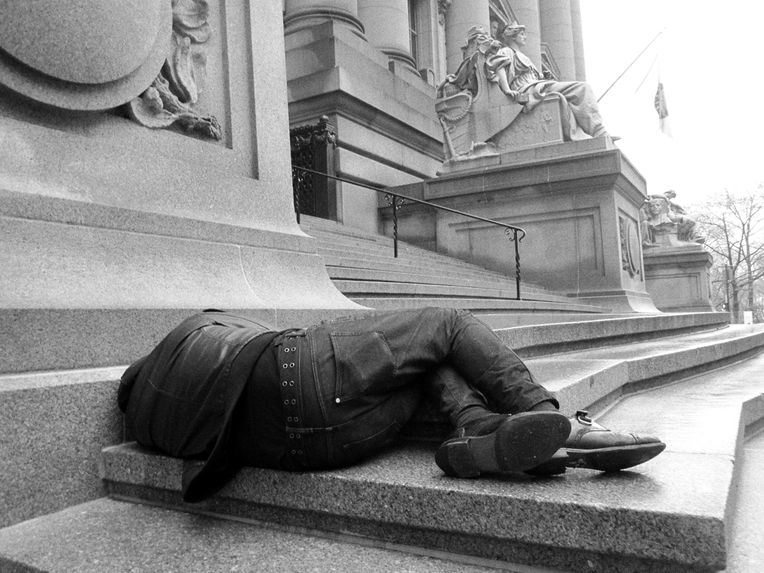 Alberto Borea,  Wall Street , 2013. Silk-screen on canvas. Courtesy of the artist and Y Gallery. [Image Description: A black and white photograph features a man laying down in the fetal position on the edge of a large, stone, stairway entrance to a government building. The man's back is to the camera. He wears jeans, leather brogues, and a leather jacket. On the staircase behind him are large marble sculptures of allegorical figures.]