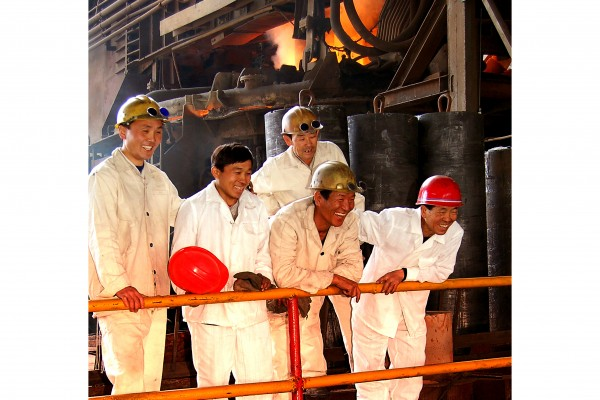 [Image Description: A photograph of five smiling men in white workers' uniforms with yellow and red hard hats lean against an orange railing looking outwards. They stand before an industrial factory, with large steel beams, cylinders, and pipes. In the distant background, there is the orange and yellow glow of a fire.]