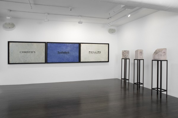 [Image Description: An installation shot features three rectangular paintings, framed in black, hung on a white wall. The paintings on the left and right have white backgrounds, while the center painting has a blue background. Written in black text on each of the paintings is the name of an auction house, from left to right: Christie's, Sotheby's, and Phillips. To the right of the paintings are three abstract marble sculptures, each mounted on black, open beamed plinths.]