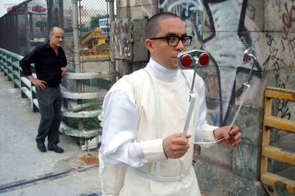 Nicolás Dumit Estévez Raful,  For Art's Sake , 2005-2007. [Image Description: The artist, Nicolás Dumit Estévez Raful, is dressed in a white, long sleeve shirt and an off-white sleeveless dress. He holds onto a contraption that is strapped to him. The contraption holds up two mirrors that he looks into in order to walk backwards. On the front of each mirror are two reflector lights. Behind him is a stone wall with graffiti tagged on it, a metal fence guarded by a short metal rail, and a bald man with a black shirt, gray slacks, and black shoes looking at the performer. Beyond the metal fence, the viewer can see into a construction site.]