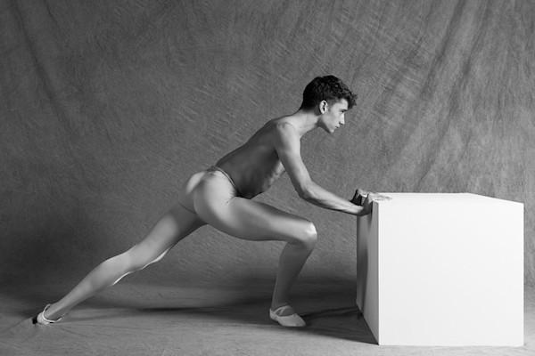 Brendan Fernandes,  The Working Move , 2012. [Image Description: A black and white photo of a shirtless dancer wearing ballet flats and tights, who stands in a lunging position with his hands gripping a white cube that is half his height. His left leg is propelled backward to give him more ability to push while his right leg is firmly in place below his chest. The background is a piece of gray fabric.]