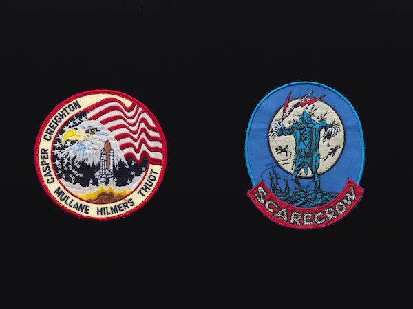 """Trevor Paglen,  Symbology, Volume IV  (detail), 2013. 20 fabric patches, framed. Courtesy of the artist and Metro Pictures, New York. [Image Description: Two circular fabric patches on a black background. On the left, a circular patch features an eagle superimposed over a flag with a rocket in takeoff at its center, with the names of astronauts """"Creighton, Casper, Mullane, Hilmers, Thuot"""" around the edge. On the right, a blue oval patch features a blue scarecrow layered over a full moon. At the base of the patch, the word """"Scarecrow"""" is embroidered in white on a red background.]"""