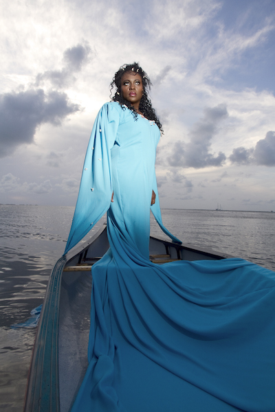Elia Alba,  The Orisha (Juana Valdes) , 2014. [Image Description: Artist Juana Valdes stands upright on a boat with her hands to her side wearing a sky blue dress with a long train that cascades before her.  The ocean surrounds the boat and whispy white, gray, and blue clouds and a blue sky provide a backdrop to her elegant and stoic stance.]