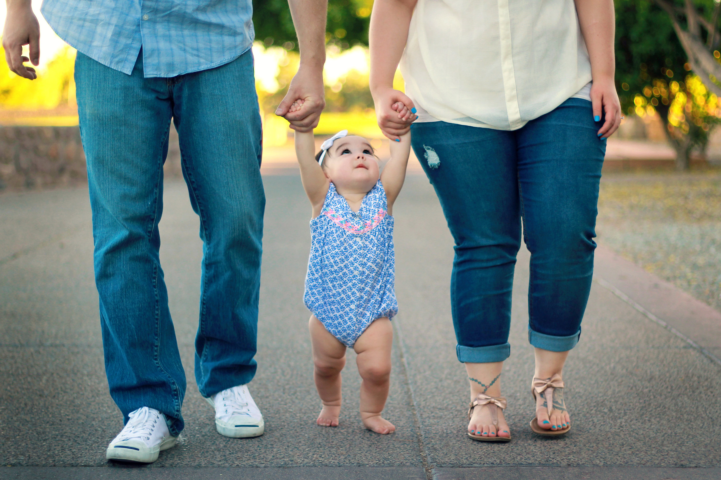 Parents helping baby walk as she gazes up at them.