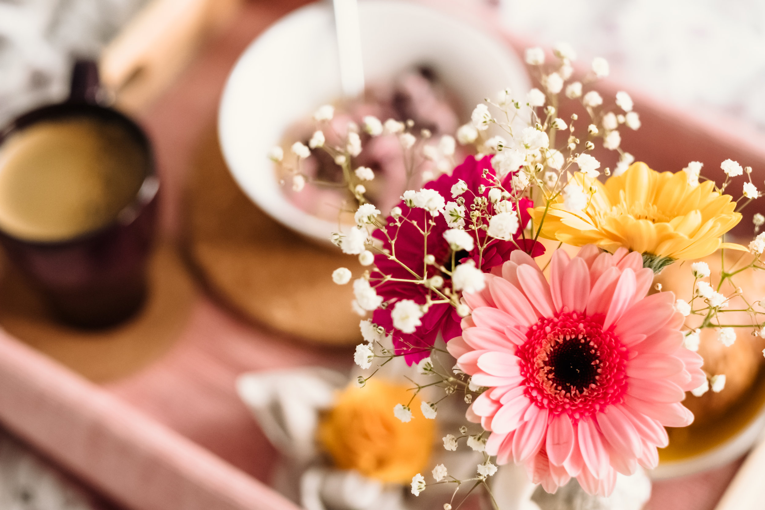 Tray with colorful flowers, coffee, and food.