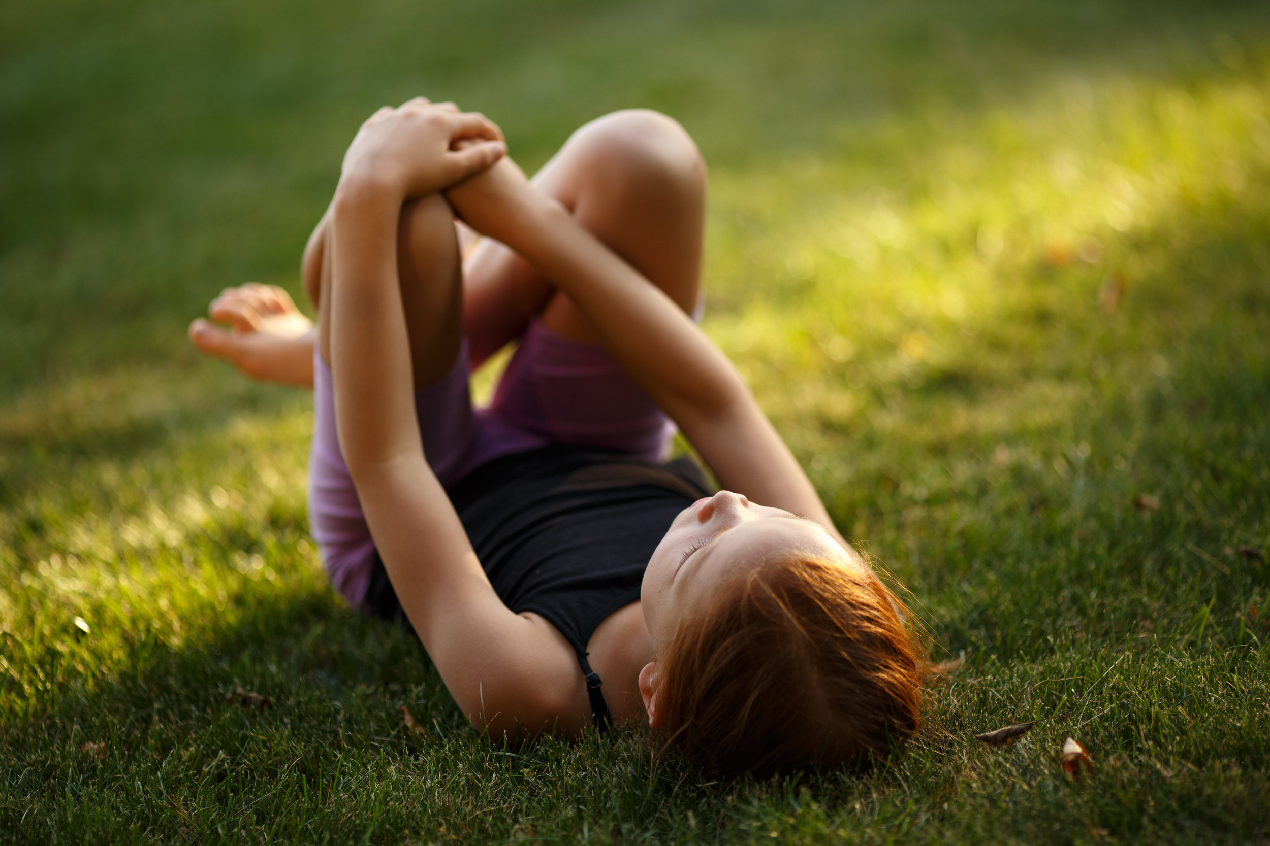 Young person lying on their back in the grass with knees up, gazing at the sky.