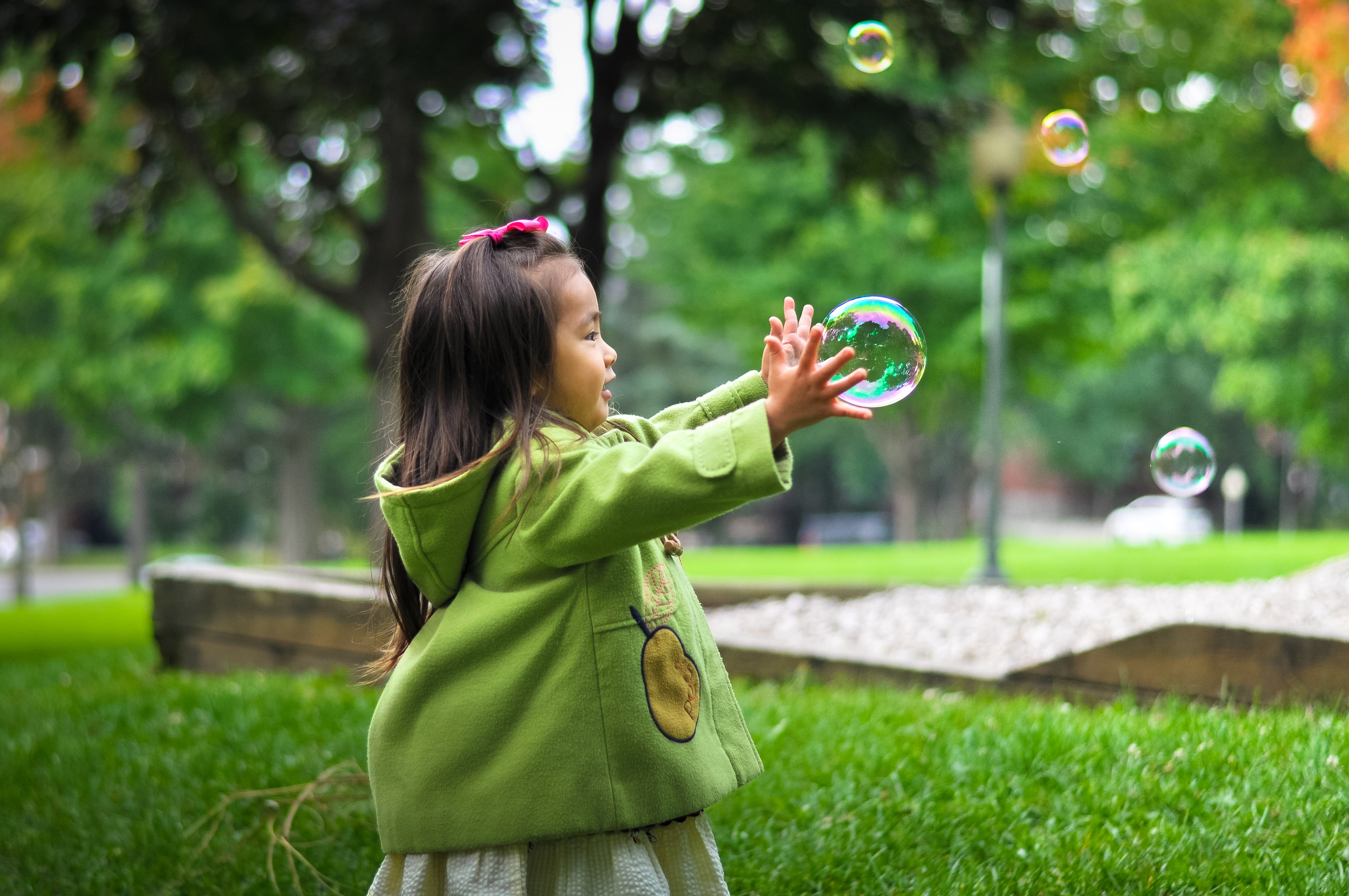 Preschool girl in a park, reaching for soap bubble as other bubbles float by.