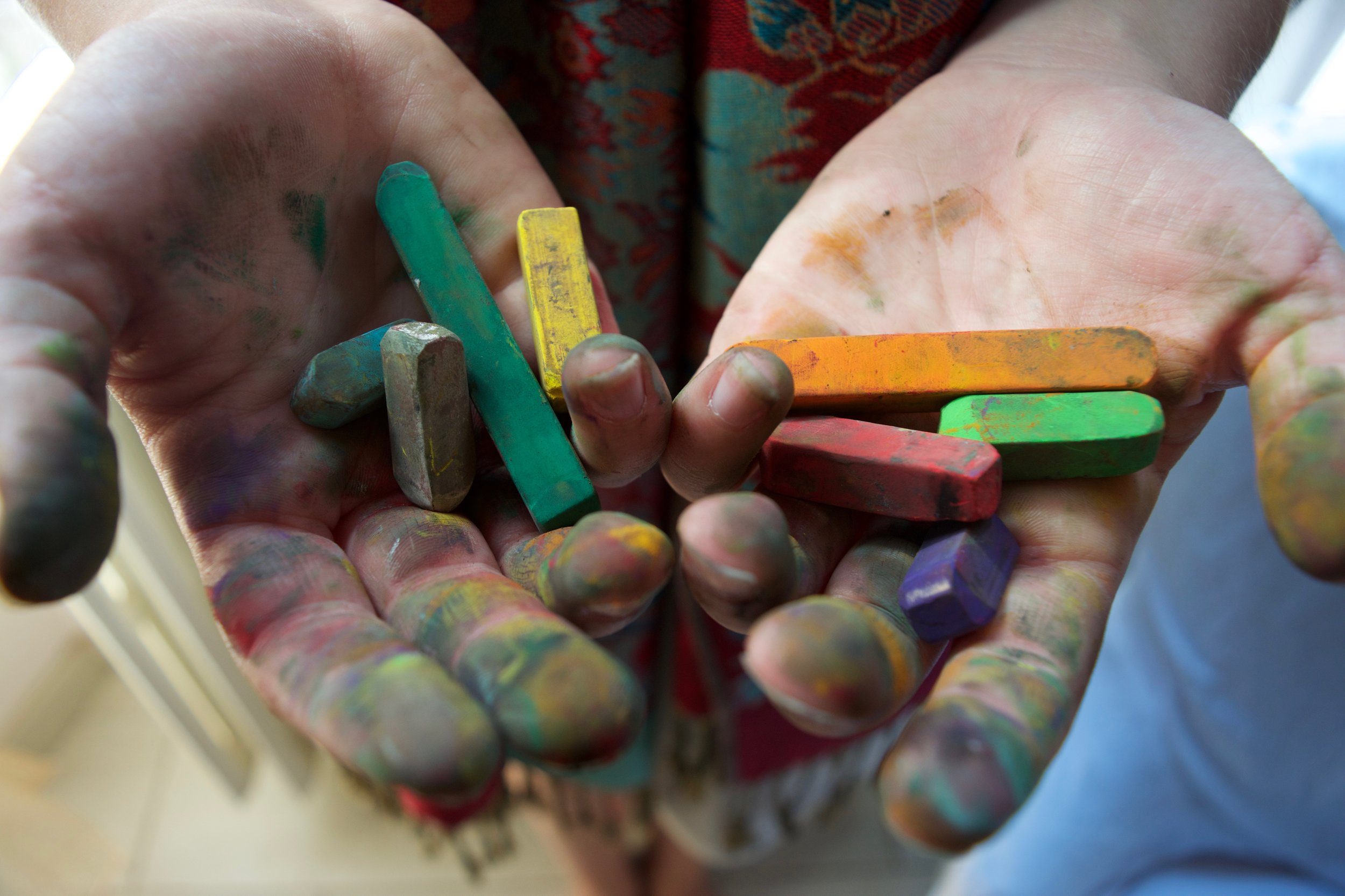 Close-up of artist's smudged hands holding colorful pastels.