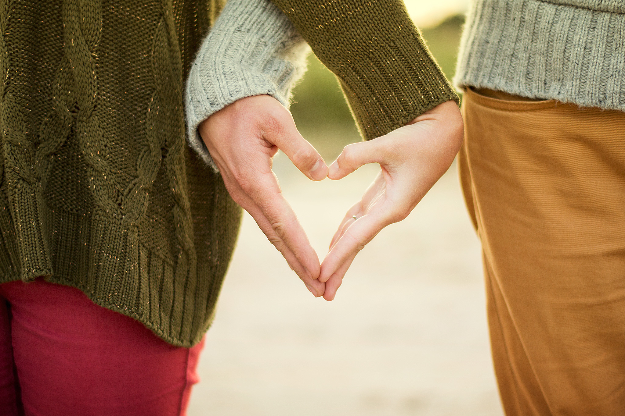 Two people side-by-side, their hands forming a heart.