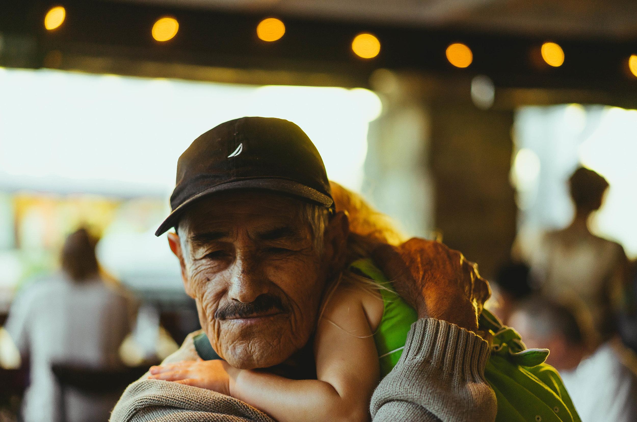 Elderly man lovingly holding sleeping toddler on his shoulders.