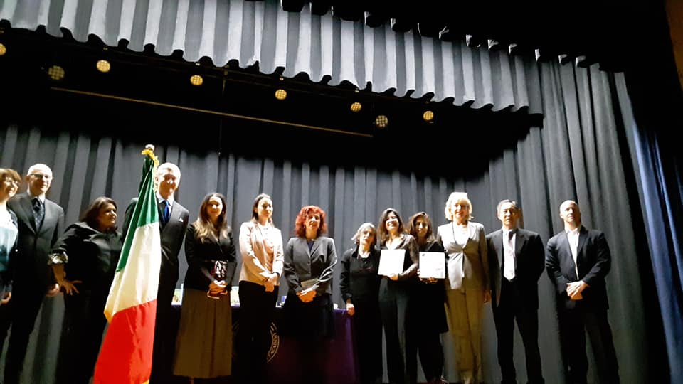 La Delegazione del Consolato d'Italia, insieme agli sponsor Illy Caffè e Rizzoli, lo staff della PS242, i rappresentanti del DOE e il trio di InItaliano durante la Cerimonia della Consegna della Bandiera presso la PS242, aprile 2019.