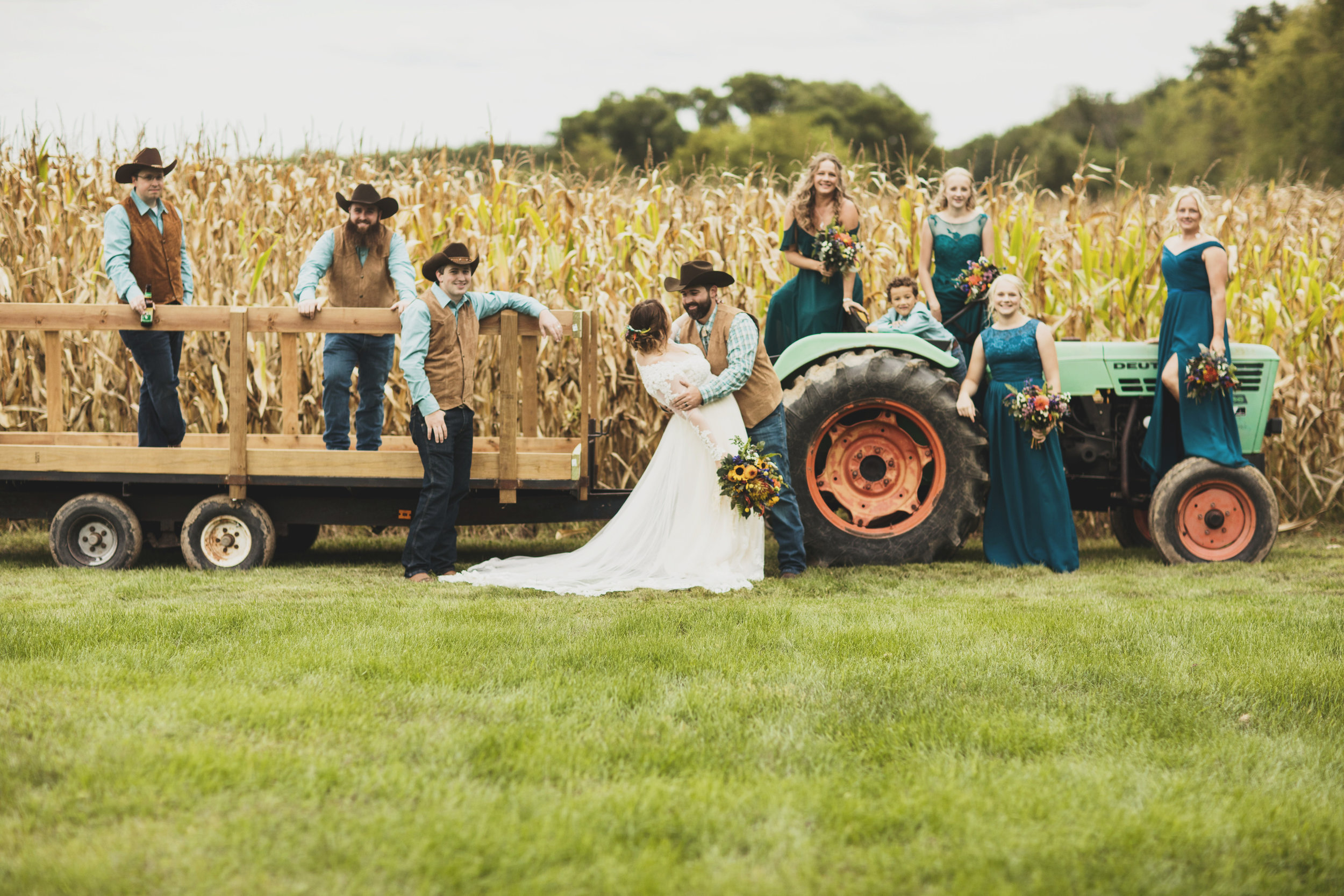 Bridal Party Poses with Tractor at Barn Wedding Venue