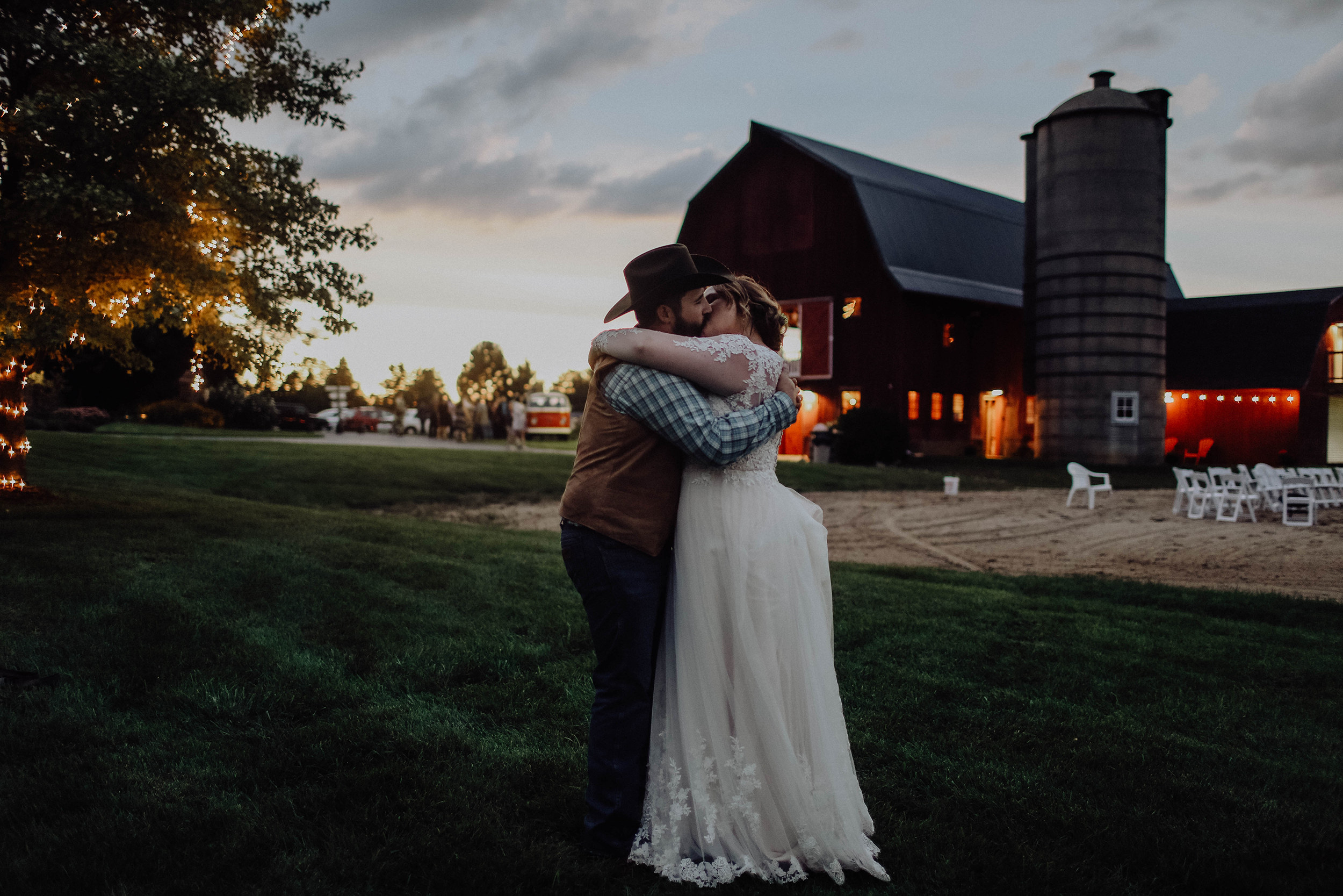 bride-groom-kiss-at-dusk-at-barn-wedding-venue.jpeg