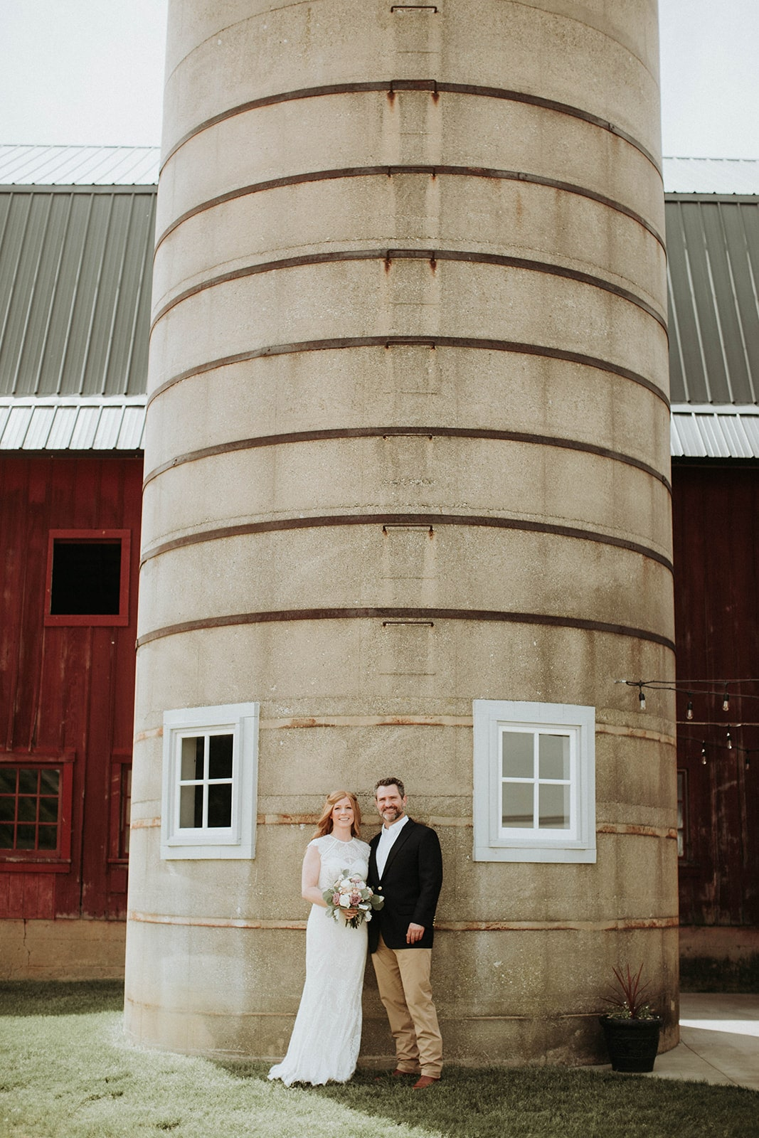 bride-and-groom-pose-by-barn-silo-min.jpg
