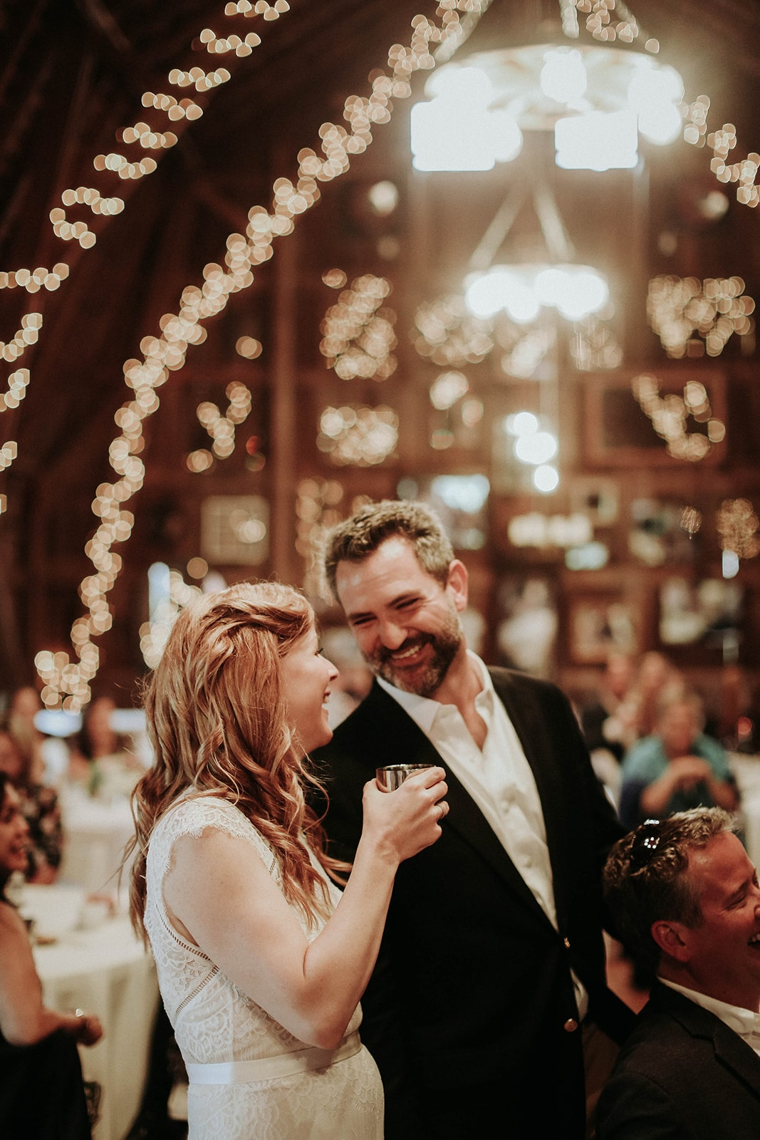 couple-shares-laugh-at-barn-venue-reception-min.jpg