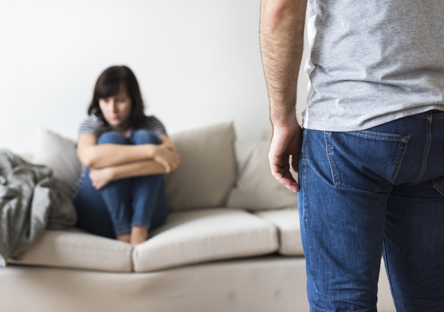 Sad woman curled up on couch while partner faces her.