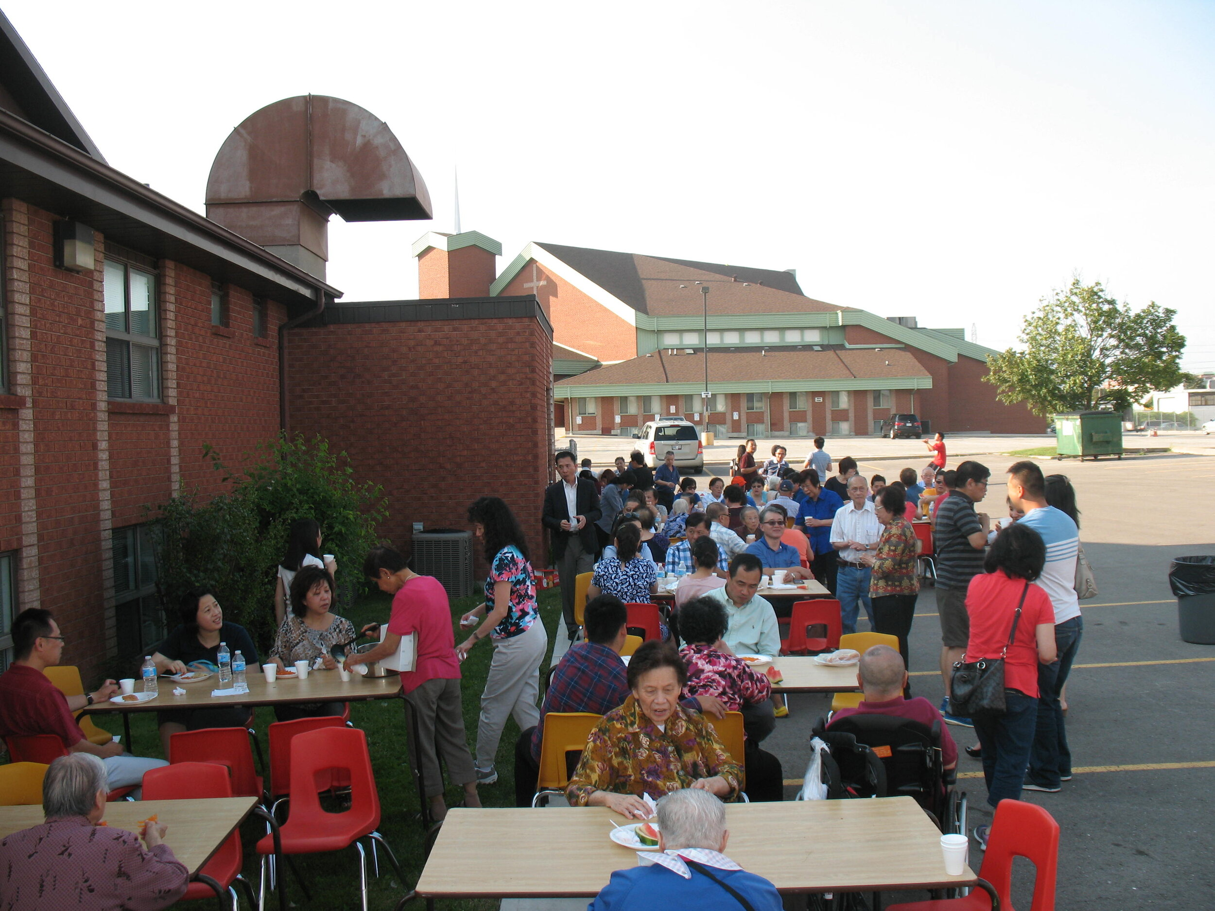 The congregants at Hakka Alliance enjoy a BBQ in the church parking lot after the service.