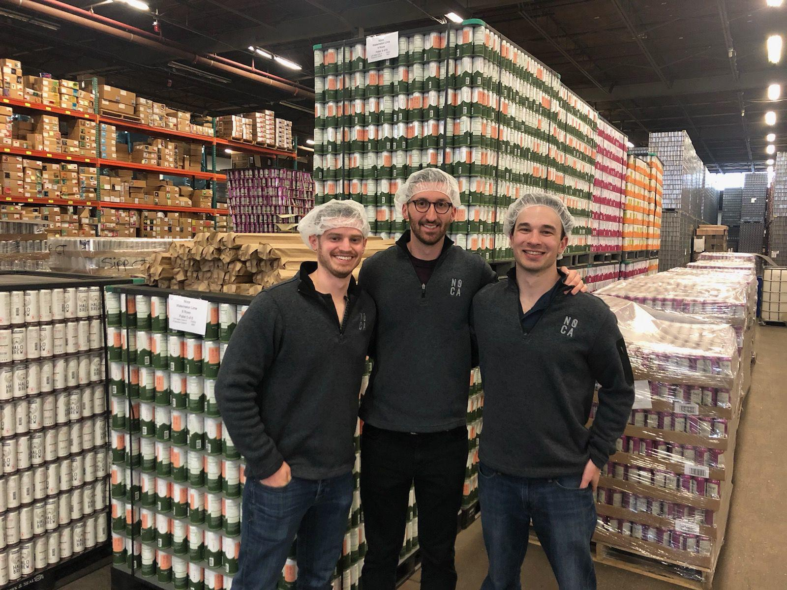 NOCA co-founders, from left, Alex Febonio, Richard Roy and Galen Hand stand by pallets of their spiked water at the plant in Baltimore where NOCA is made and packaged.