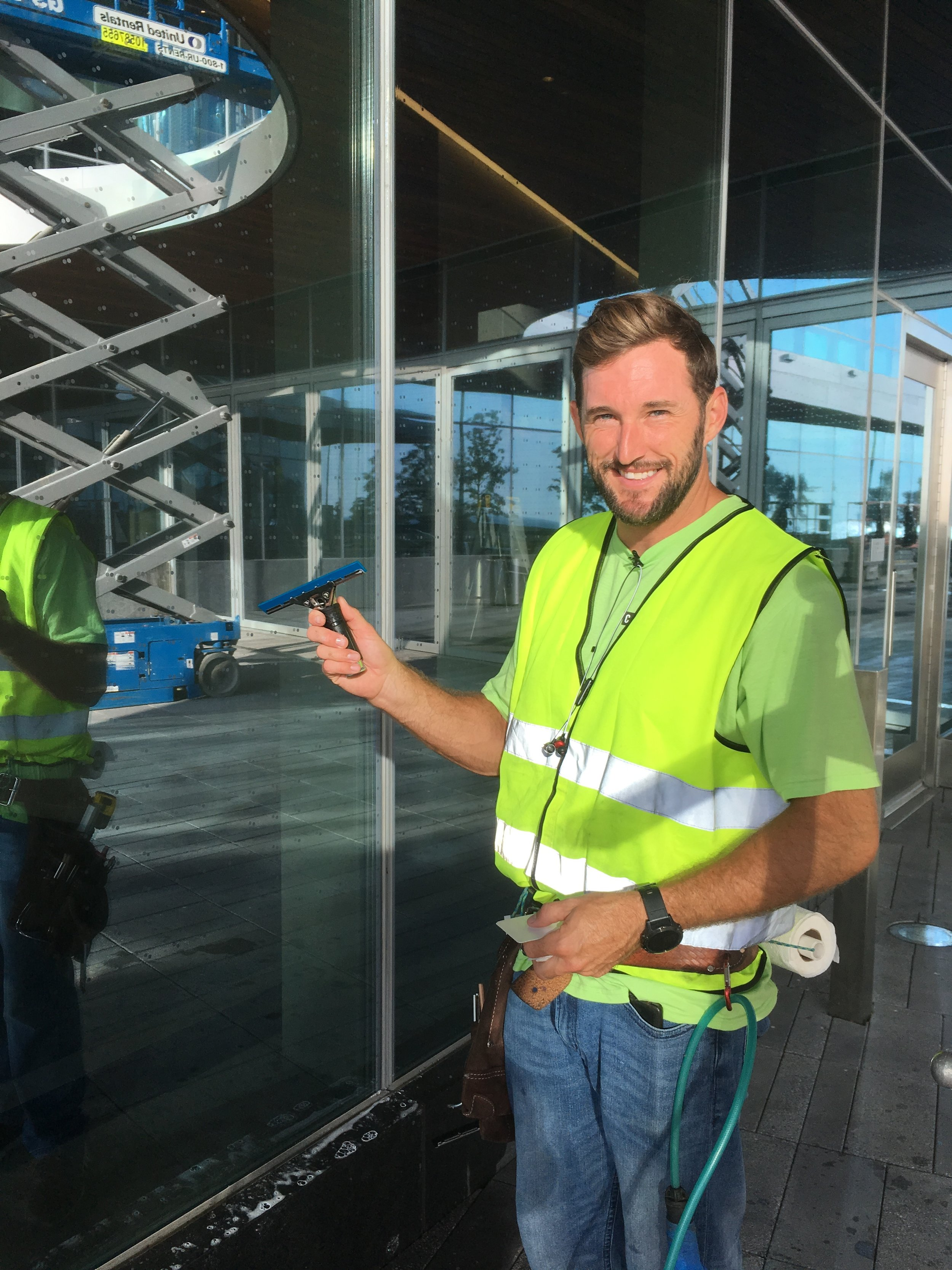 This worker is retrofitting reflective glass with film that has a bird-friendly dot pattern (look closely). Including fritted glass in the design of this large building would have saved money… and bird lives!