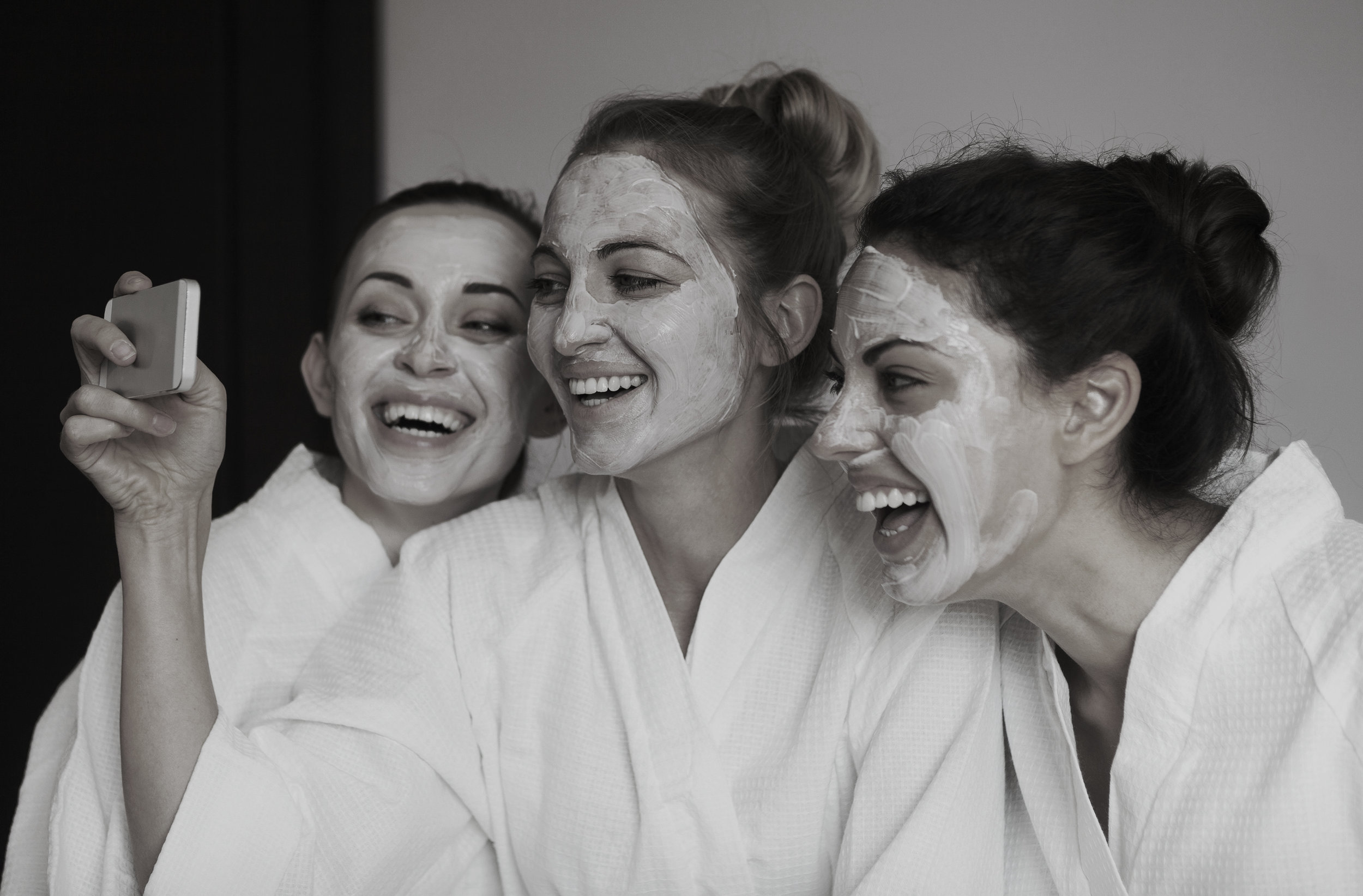 Testimonials at Hela Medical Spa, image showing three women with facials having a spa party