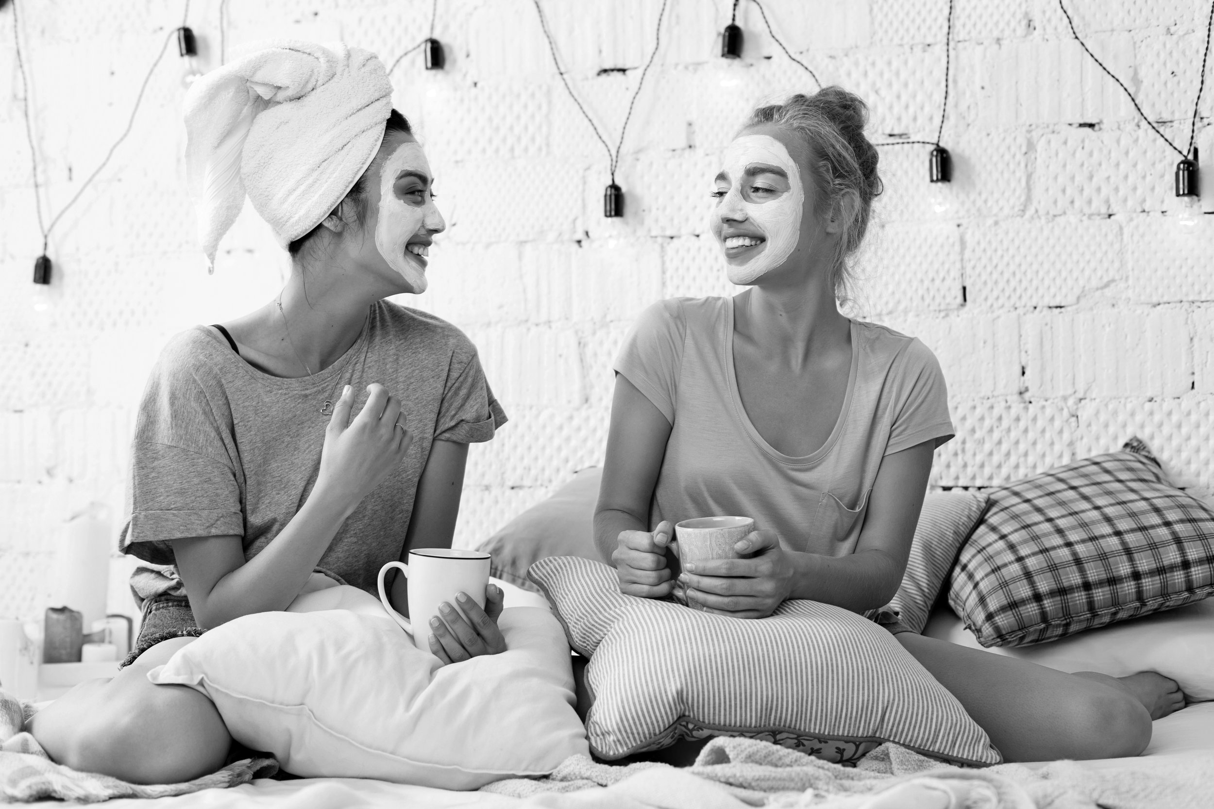 Two women relaxing enjoying facial skincare masks