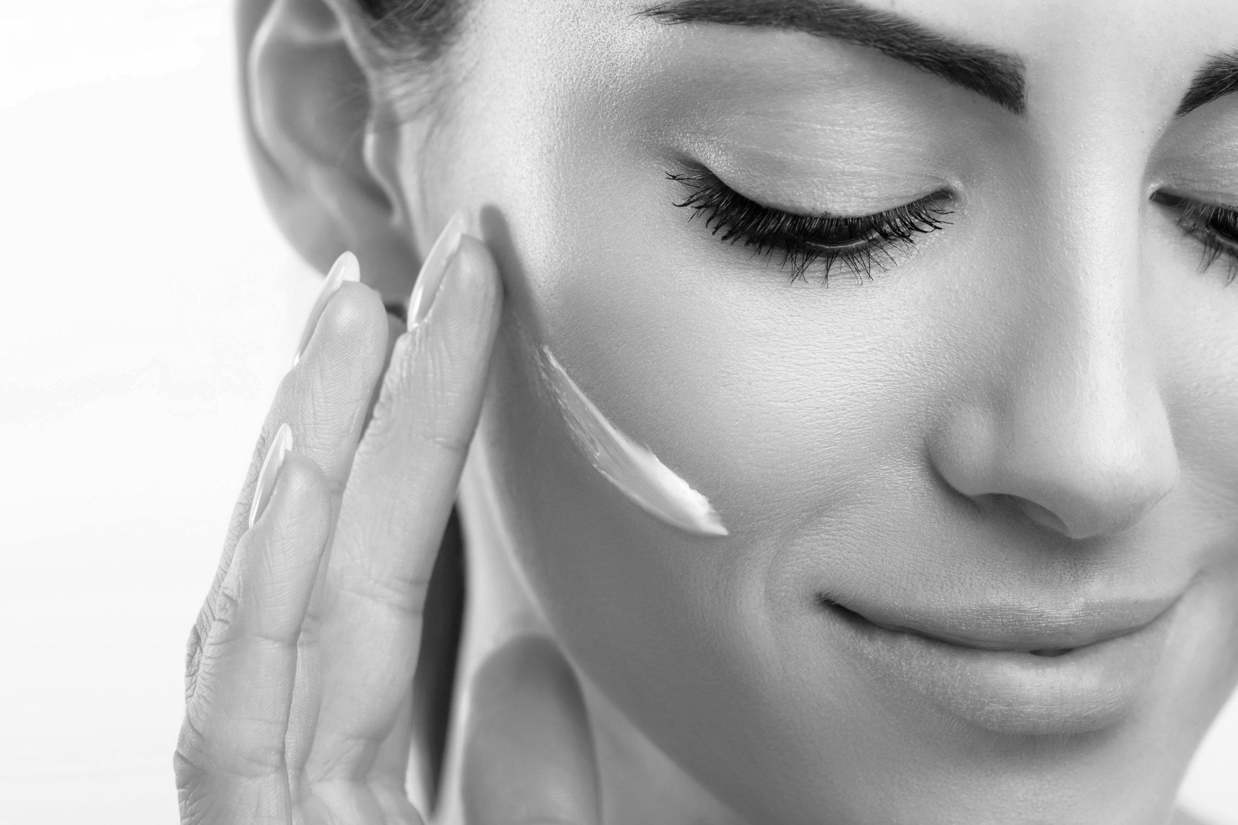 Woman applying natural skincare facial cream
