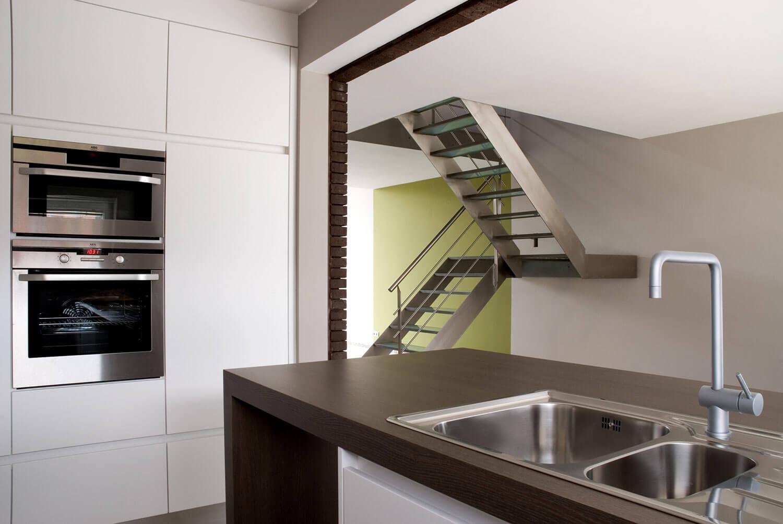 De stalen trap werkt als opdelend element tussen keuken en woonkamer, maar behoudt de maximale doorkijk van het gebouw.