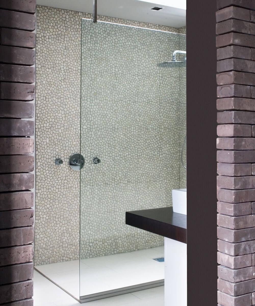 De douchewand werd afgewerkt met een eenvoudig reinigbare mozaïeksteen.