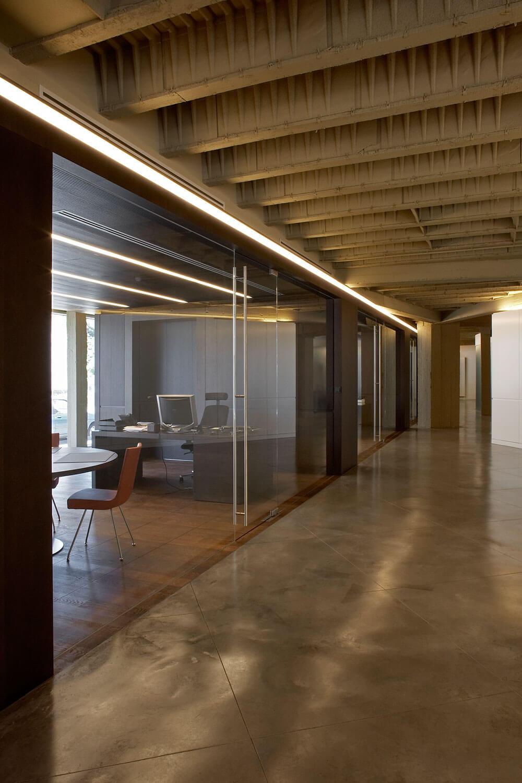 De volledig glazen wanden geven het geheel een zeer ruimtelijk gevoel. Ook het licht, dat langs de ramen van de kantoren binnenkomt, bereikt op deze manier de hal.