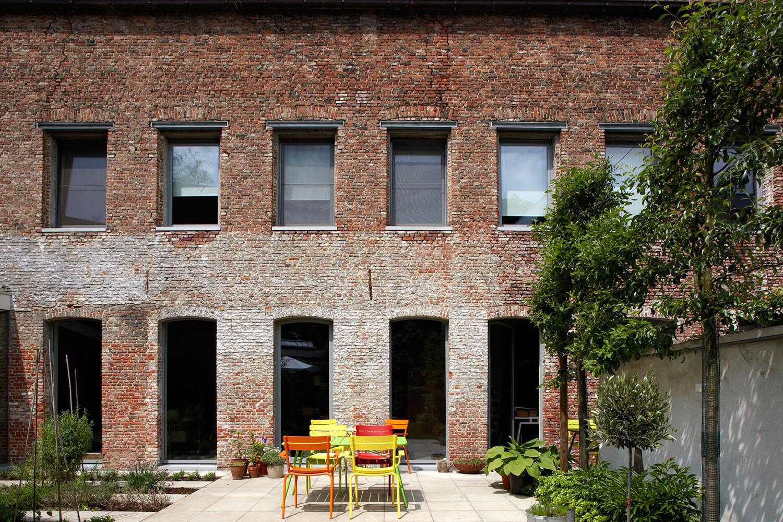 Zicht vanuit de tuin naar het terras en woonhuis