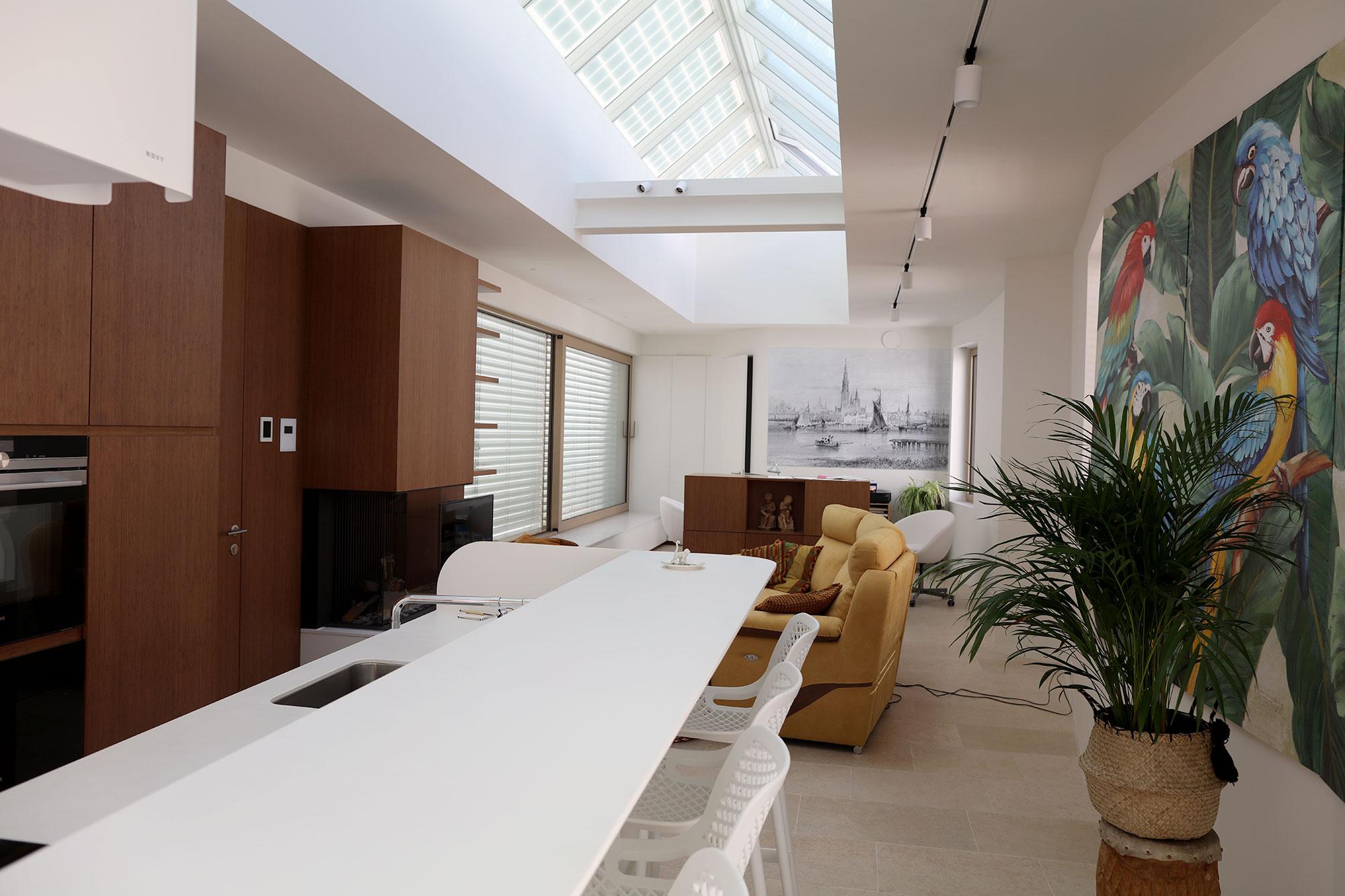Interieur van de gerenoveerde woonkamer, voorzien van een lange lichtstraat geplaatst in het dak. Op maat gemaakt interieur ontworpen door AAA.