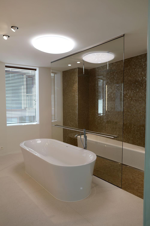 Minimalistisch badkamerinterieur, voorzien van badkuip en ruime inloopdouche met zitbank.