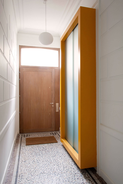 De kast aan de ingang werd gerealiseerd in hetzelfde gele kleuraccent dat is terug te vinden doorheen de woning.