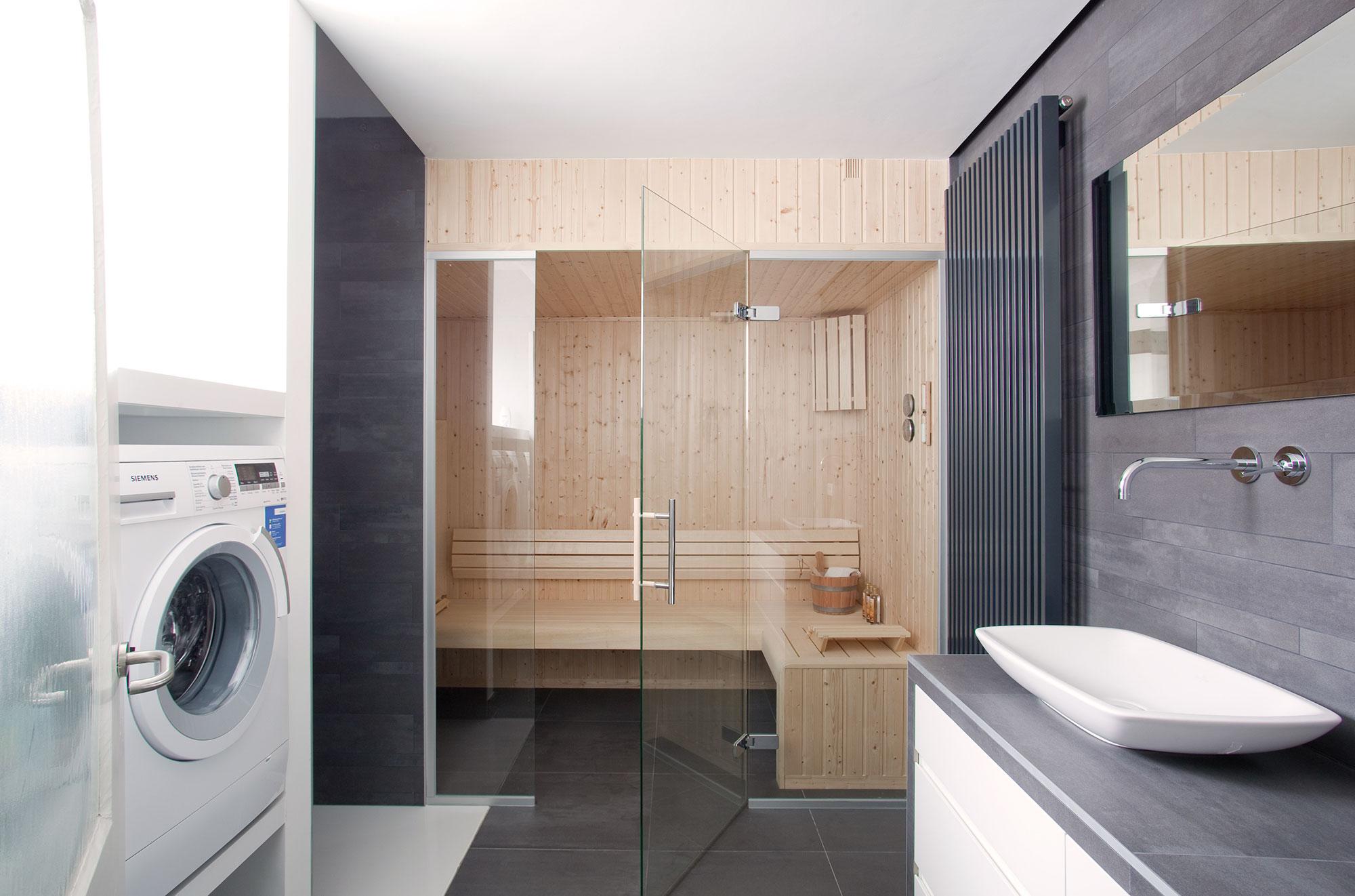 De badkamer werd voorzien van een sauna. Door deze af te sluiten met een glazen deur, gaat de openheid van de ruimte niet verloren.