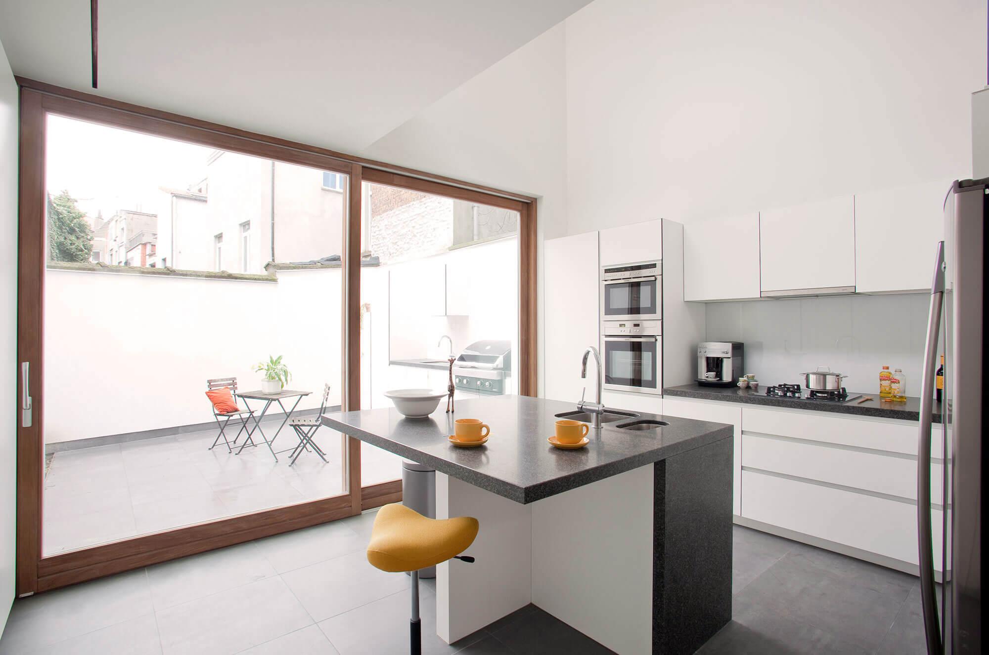 De keuken, voorzien van een kookeiland, sluit aan op de binnenkoer. De grote schuiframen zorgen voor een maximale natuurlijke belichting van de ruimte.