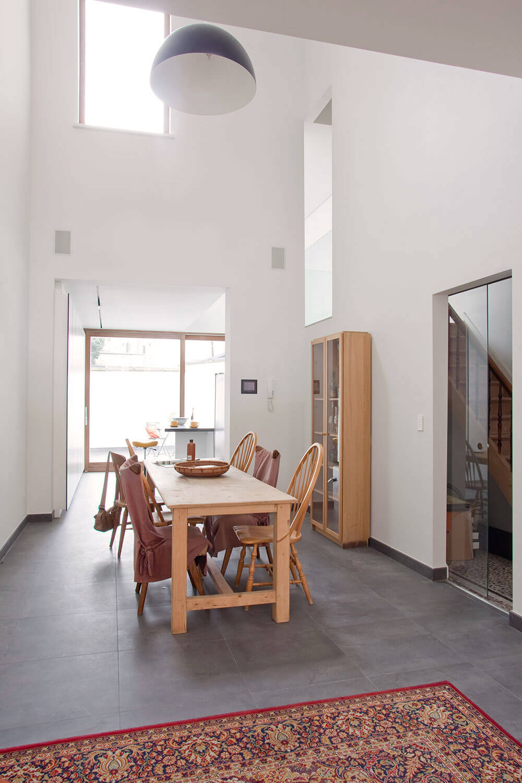 De eetruimte is licht en luchtig door de enorm hoge plafonds en de aanwezigheid van vele ramen.