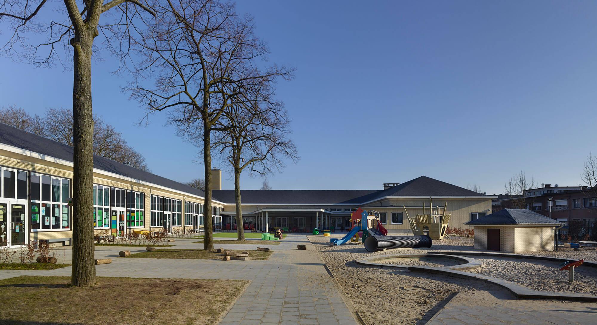 Overzicht van de ruime speelplaats, voorzien van een grote en open zandbak.
