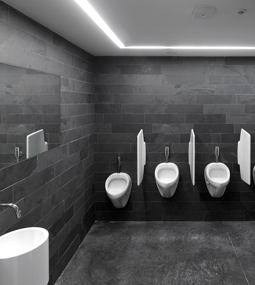De mannentoiletten werden afgewerkt met donkere natuursteen en heldere lichtlijnen.