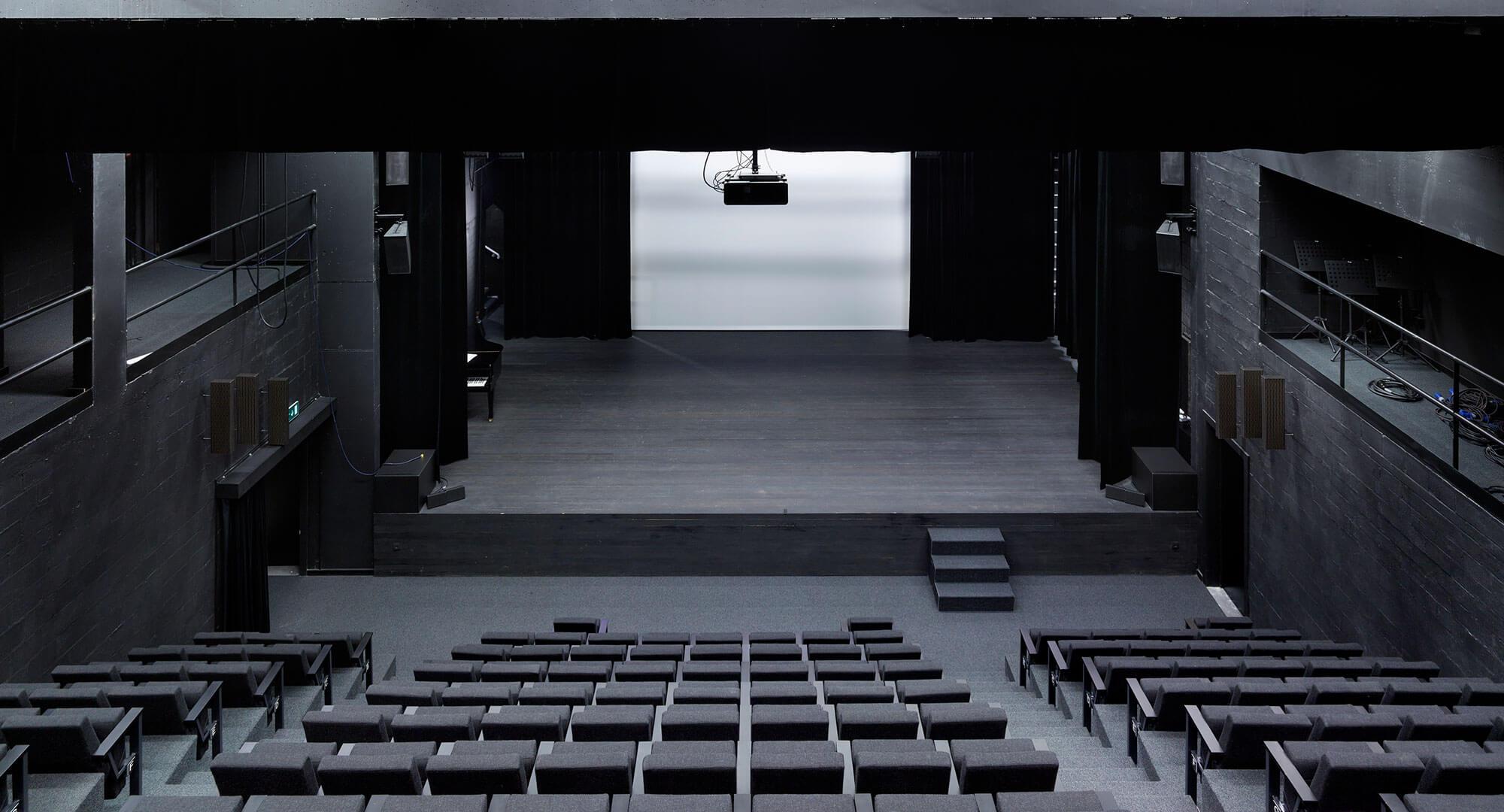 Beeld van het podium. De volledige zaal werd in zwart afgewerkt voor een uniforme en strakke look.